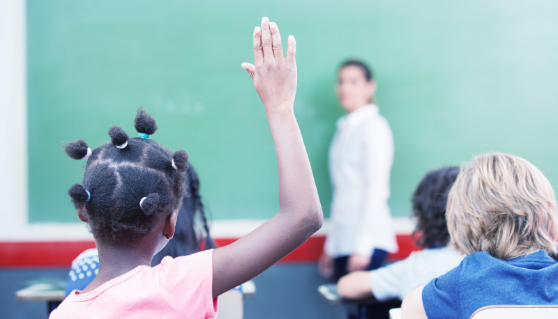 Afroamerican female student raising hand at school