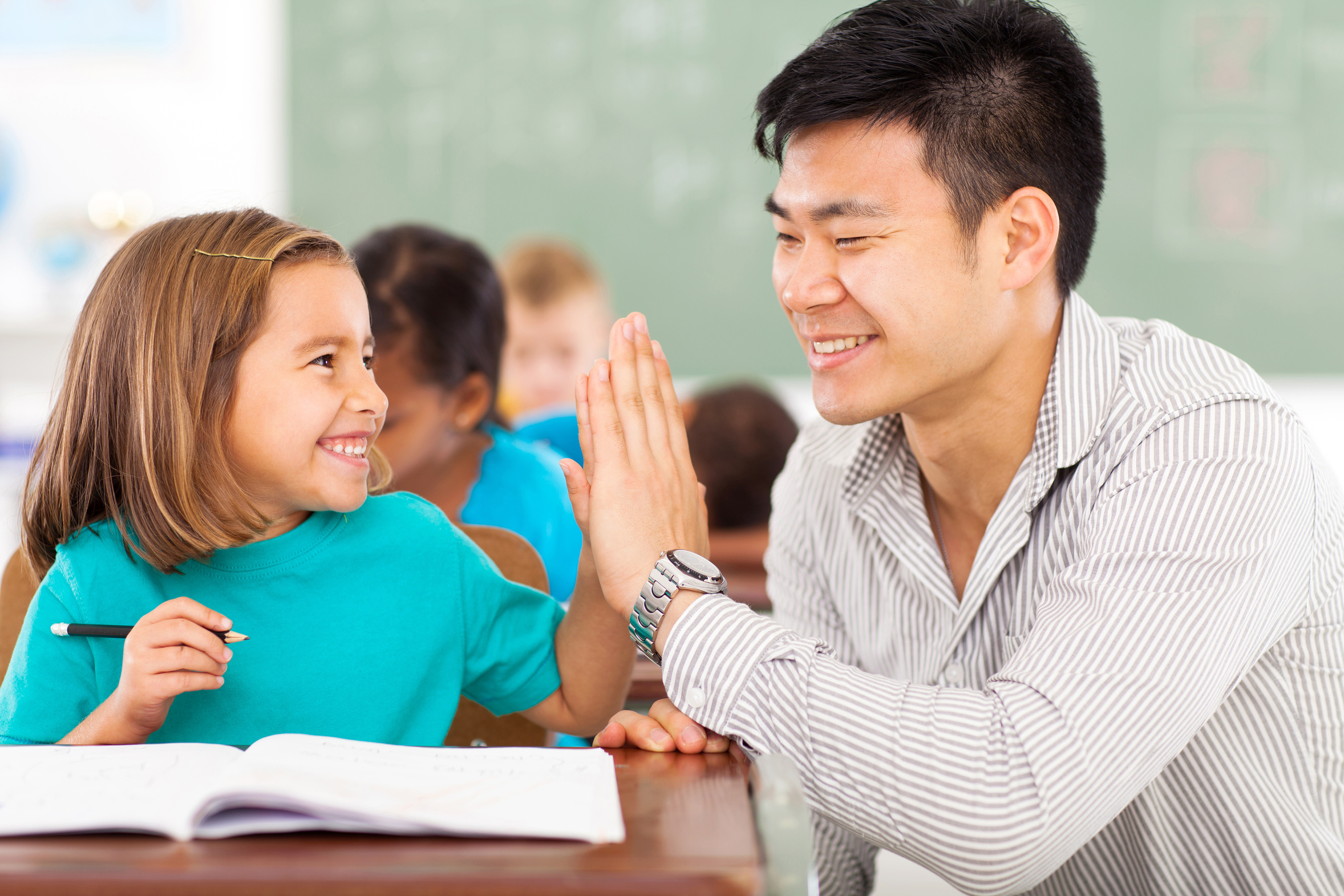student and teacher high-fiving in class