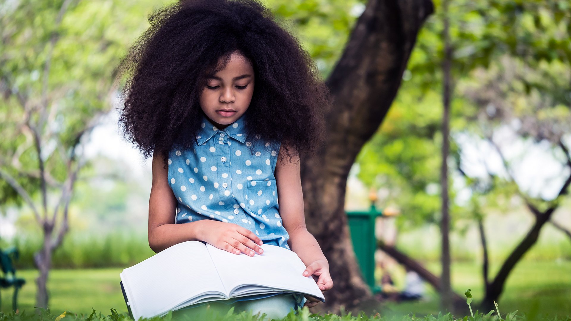 young girl reading book outside in summer
