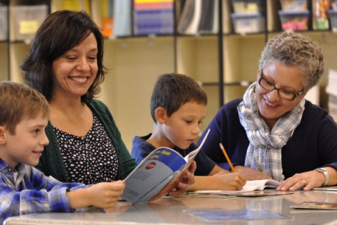 teacher and paraeducator with students