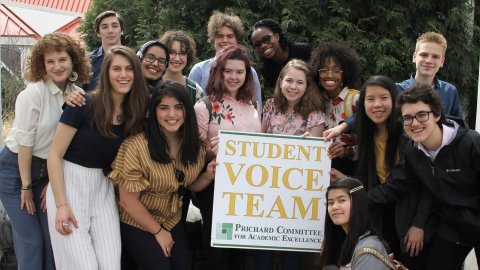 Members of the Student Voice Team pose with a sign