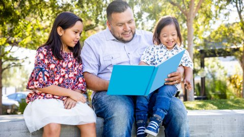 A father reads to his two daughters outside