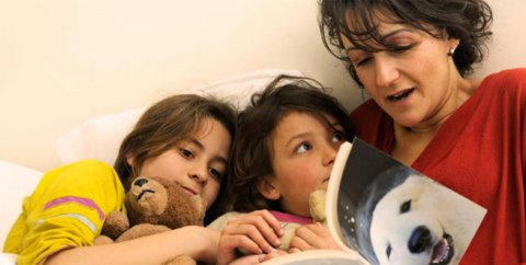 A mom reads a book to her children in bed