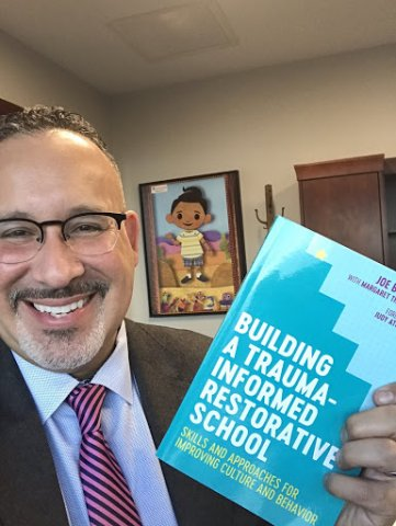"Miguel Cardona holds a book with the the title ""Building a Trauma-Informed Restorative School"