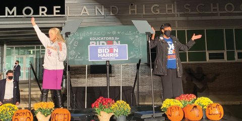 Jill Biden and NEA President Becky Pringle on a stage together with a Biden-Harris campaign sign behind them.