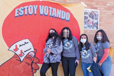 """Students activists with the group Youth Empowered in the Struggle (YES) wear masks while standing in front of a sign that says, """"Estoy Votando."""""""