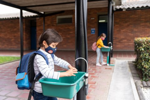 Child in mask washing hands