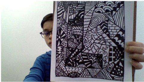 Fifth grader displays his Zentangle art project.