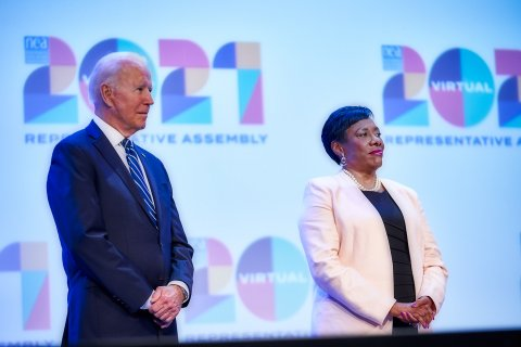 President Joe Biden and NEA President Becky Pringle stand next to each other in front of the 2021 NEA RA logo